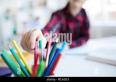 Hand of contemporary schoolgirl taking one of crayons from box before drawing at lesson - Stock Image