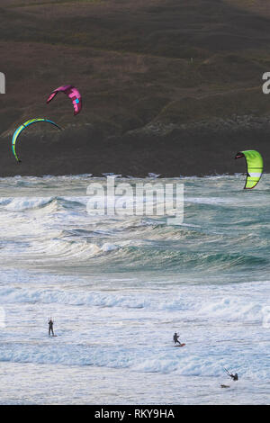 Kiteboarders kitesurfing in rough sea at Crantock Beach in Newquay in Cornwall. - Stock Image