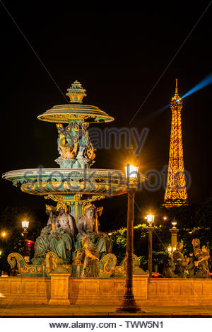 One of the two monumental fountains at Place de la Concorde. This one is called 'Fountain of the RIvers.' The illuminated Eiffel Tower is the backgrou - Stock Image
