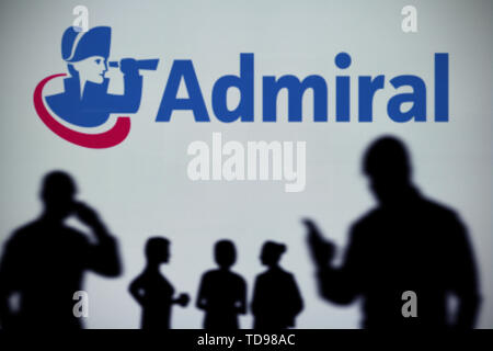 The Admiral Insurance logo is seen on an LED screen in the background while a silhouetted person uses a smartphone (Editorial use only). - Stock Image