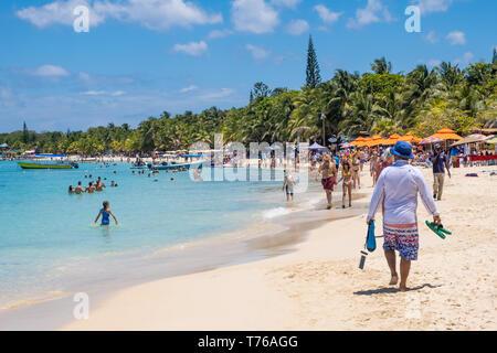 People enjoying the beach at West Bay Roatan Honduras on a beautiful sunny April day. - Stock Image