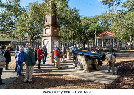 A tour group visits a monument and cast iron gun at the Plaza de la Constitucion in the historic district of Saint Augustine, Florida USA - Stock Image