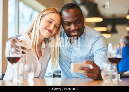 Enamored young couple taking a selfie photo while rendezvousing in the restaurant - Stock Image