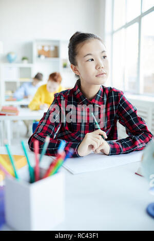 Pensive little girl thinking of idea while sitting by desk at lesson of drawing and looking through window - Stock Image