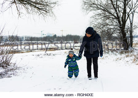 Poznan, Poland - January 26, 2019: Woman holding hand of small toddler boy while walking on snow at a park on a cold winter day. - Stock Image
