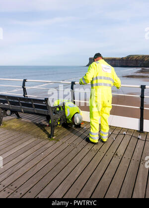 EElectricians rigging decorative strings of lights on the deck of Saltburn Pier - Stock Image
