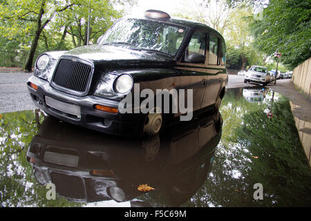 black cab taxi in puddle or rain water on london road england uk - Stock Image