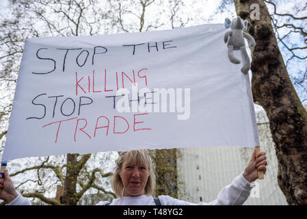 Protester at a stop trophy hunting and ivory trade protest rally, London, UK. Banner requesting stop the killing, stop the trade. Female - Stock Image