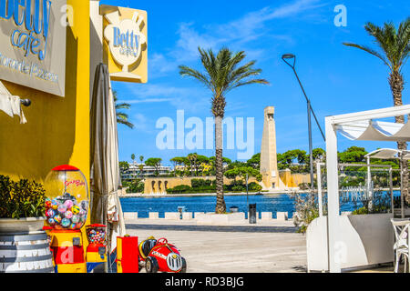 View from a sidewalk cafe of the Italian Sailor Monument, promenade and bay in the port city of Brindisi Italy in the Southern region of Puglia. - Stock Image