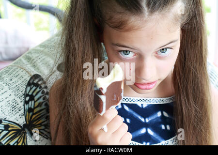 Young girl / child eating a messy dripping chocolate ice cream on a stick. Extreme shallow depth of field with selective focus on girls eyes and not i - Stock Image
