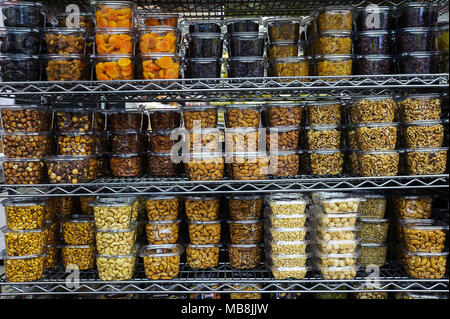 Pile of various dried fruit and nuts packaged in airtight transparent plastic containers for convenience and freshness, positioned on a metal rack - Stock Image