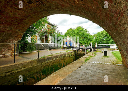 Bottom lock on Foxton flight and the lock keepers cottage viewed through the archway of the bridge over the canal - Stock Image