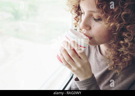 Close-up portrait of a beautiful and young woman with blue eyes and curly blonde hair drinks coffee or tea while she is in a journey - Stock Image