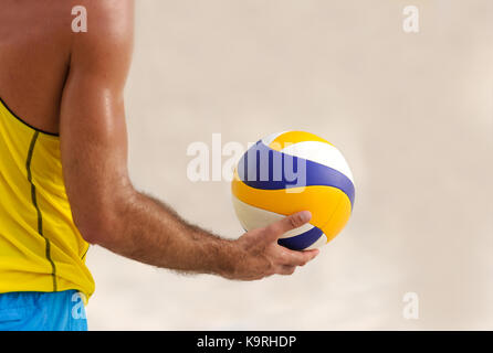 Volleyball is a male volleyball player getting ready to serve the ball. - Stock Image
