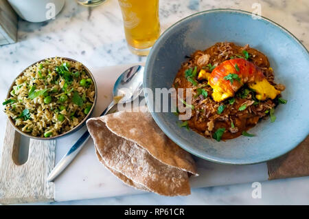 A bowl of Monk Fish  Curry, topped with a Tiger Prawn, served with Cumin and Pea Basmati Rice and a home made Chapati   ' - Stock Image