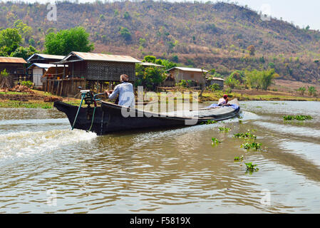 Long-tail boat(named for its long out board drive shaft)travels along shallow river  waterway that leads southernend - Stock Image
