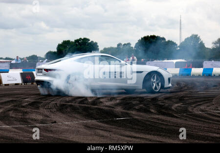 Drifting demonstration performed in a Jaguar F-Type S in the adrenaline zone of the Silverstone Classic 2017 - Stock Image