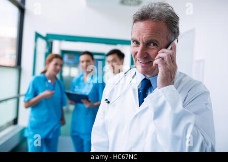 Portrait of smiling doctor talking on mobile phone in corridor - Stock Image