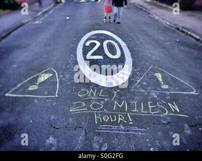 Speed limit sign on residential street. With children's graffiti, road safety. - Stock Image