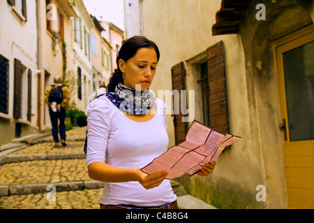 Arles; Bouches du Rhone, France; A young woman consulting her map in one of the typical streets. MR. - Stock Image