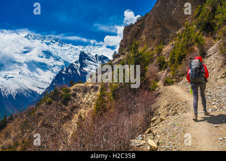 Young Pretty Woman Wearing Red Jacket Backpack Trail Mountains.Mountain Trekking Rocks Path. Snow Landscape View - Stock Image