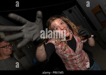 Chertsey, UK. 4th October 2018. Thrill seekers try the scare mazes of Fright Night at Thorpe Park. Actors dressed in horrific costumes provide the jumps. Credit: Thomas Faull/Alamy Live News Credit: Thomas Faull/Alamy Live News - Stock Image