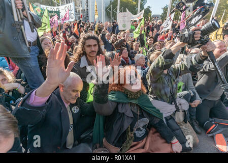 London, UK. 31st October 2018. People  blocking the roadway in front of Parliament after making the 'Declaration of Rebellion' against the British Government for its criminal inaction in the face of climate change catastrophe and ecological collapse raise their hands to continue their occupation. They listened to speeches by George Monbiot and Green Party MP Caroline Lucas and there were songs and poems. A number of activists brought large wreaths and lay down with them, with several lock-ons. Police tried to clear the road, but the protesters ignored them, taking a show of hands to remain blo - Stock Image