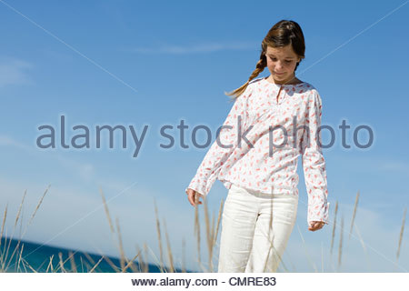 Girl walking by coast - Stock Image