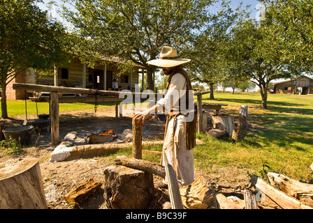 Settler chopping wood 1830s Jones Stock Farm George Ranch Historical Park Houston texas tx tourist attraction - Stock Image