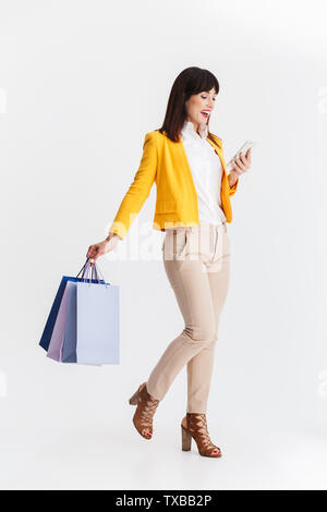 Image of a beautiful young business woman posing isolated over white background using mobile phone holding shopping bags. - Stock Image