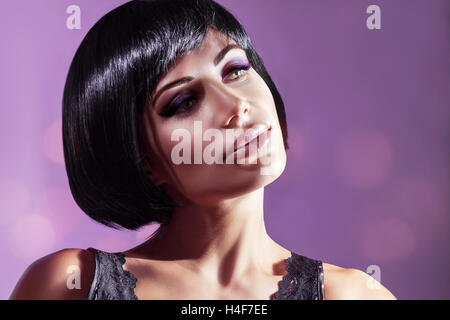 Portrait of a beautiful young woman over purple background, attractive model with gorgeous bob haircut and bright - Stock Image