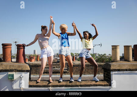 Carefree young women friends dancing on sunny summer rooftop - Stock Image