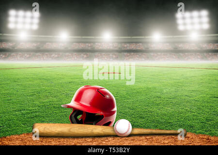 Baseball helmet, bat and ball on field at brightly lit outdoor stadium. Focus on foreground and shallow depth of field on background and copy space. - Stock Image