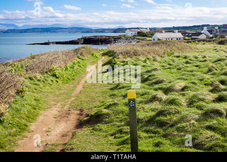 Anglesey coastal path and sign on Welsh coast with view to distant mountains. Moelfre, Isle of Anglesey, Wales, UK, Britain - Stock Image