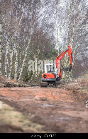 Kubota KX 161-3 mini excavator operating along a moorland track. - Stock Image