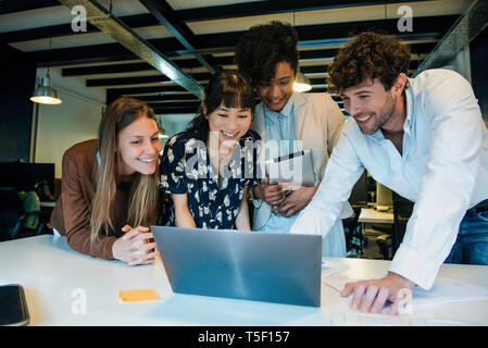 Business people using laptop in office - Stock Image