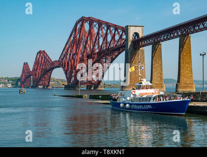 South Queensferry, Scotland, United Kingdom, 15 May 2019. UK Weather: Gorgeous sunny warm day along the Firth of Forth coast at the iconic Forth Rail Bridge and a tourist boat loading passengers. Credit: Sally Anderson/Alamy Live News - Stock Image