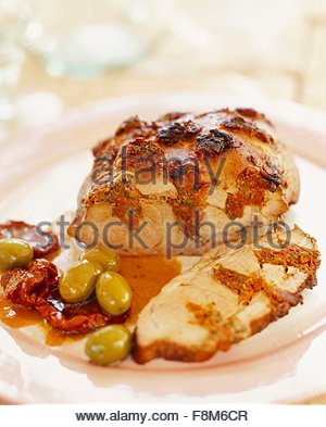Roast pork stuffed with dried tomatoes and olives - Stock Image