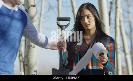 Low angle view of boyfriend comforting upset girlfriend with toilet paper and shovel in remote woods - Stock Image