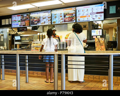 Woman and young girl being served inside in line at a Burger King fast food restaurant in Montgomery Alabama, USA. - Stock Image