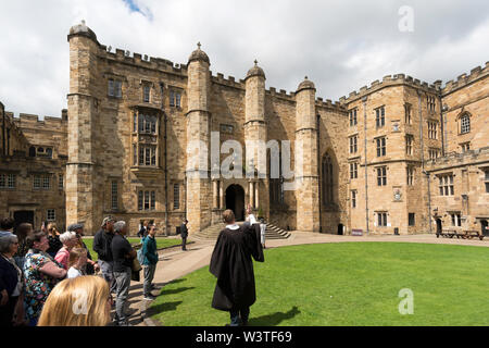 A group of visitors with a postgraduate tour guide in the courtyard of Durham Castle, part of University College Durham, England, UK - Stock Image