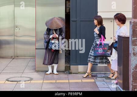 A Shintoist monk asking for alms in the street in Fukuoka, Japan. - Stock Image