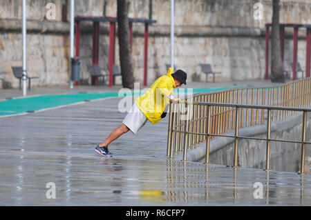 Man exercising in the rain - Stock Image