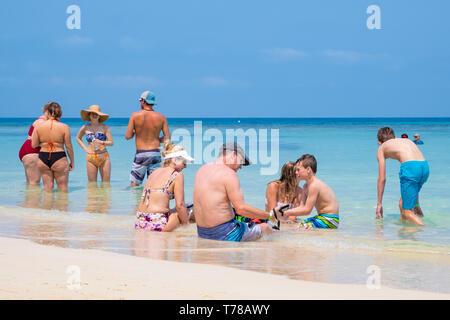 Tourists enjoy the warm clear waters of West Bay Roatan Honduras. - Stock Image
