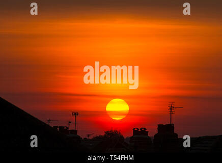 London, UK. 20th April, 2019. Sun sets over suburban rooftops in a clear orange sky after a day of cloudless skies and soaring summer temperatures during Easter holiday weekend. Credit: Malcolm Park/Alamy Live News. - Stock Image