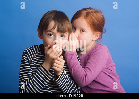 Girl aged 6 and boy 8 on a blue background whispering in ear to improve hearing. Showing use of the sense to hear. - Stock Image