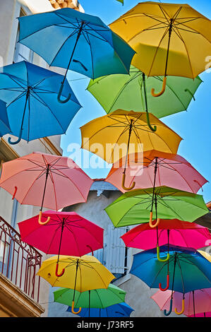 Colourful umbrellas hanging between buildings above a street in the old town area of Beziers, France - Stock Image