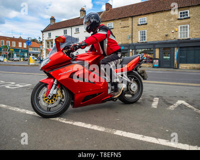 A motor cyclist riding a red Aprilia Futura Motor cycle pulling up at a Favorite stopping place in Helmsley Market North Yorkshire - Stock Image
