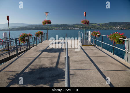 Meilen, Zurich, Switzerland. 13th Oct, 2018. September 12, 2018. A pier in Meilen on the Zurichsee has colorful geraniums in bloom on a sunny fall day. Credit: Ralph Lauer/ZUMA Wire/Alamy Live News - Stock Image