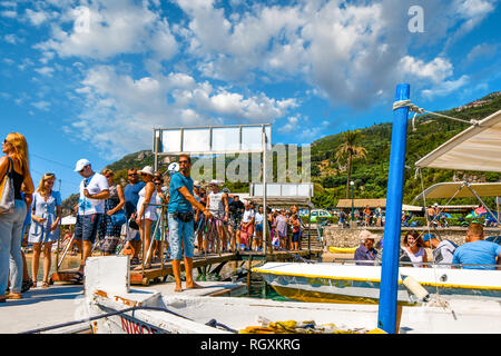 Corfu, Greece - September 20 2018: A tour boat leader maintains the boats in dock as tourists line up at Palaiokastritsa Beach on the island of Corfu - Stock Image